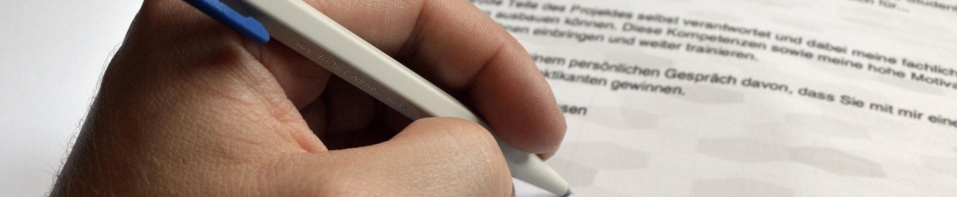 Schrijven van sollicitatiebrief met pen
